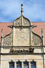 Neogotische Giebel mit Blattschmuck und Adlerrelief - Schriftzug Deutsche Post; neugotischer Baustil der Hauptpost in Dessau-Roßlau.