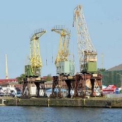 Alte Hafenkräne / Bauform Wippkran stehen an einem Kai an der Oder in Stettin