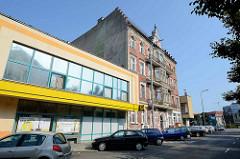 Moderner Flachbau, daneben ein Wohnhaus mit Gründerzeitfassade weiß abgesetzten Fenstern - Architektur neu + alt in der Stadt Stettin.