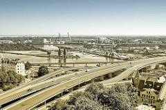 Luftaufnahme vom Hafengebiet einer oder in Stettin; moderne Autobrücken führen über den Fluss, rechts unten der Frauentum.