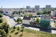 Blick vom alten Räucherturm in Dessau-Roßlau; im Vordergrund ein restauriertes Haus, eine Hausruine mit Baumwuchs.