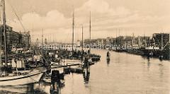 Historisches Foto vom Hafengebiet an der Oder in Stettin; Schiffe liegen dicht gedrängt an der Hafenpromenade, dahinter Wohnhäuser / Geschäftshäuser.