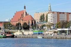 Blick über die West-Oder zu Uferpromenade in Stettin; gotisches Bauwerk / Backsteingotik der St.-Johannes-Evangelist-Kirche (Johanneskirche).