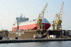 Ein Schiff liegt im Trockendock dder Stettiner Werft / Stocznia Szczecińska.