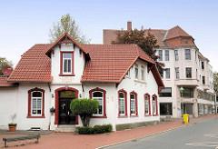 Historisches Wohngebäude / Einzelhaus mit rot abgesetzten Fenster- / Türumrandung; lange Straße in Bremerhaven
