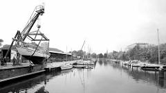 Blick in den Hauptkanal von Bremerhaven zur Marina  Weser Yacht Club; eine Segelyacht wird gekrant, um in das Winterlager gebracht zu werden.