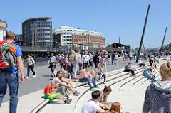 Elbpromenade an den Vorsetzen / Baumwall in der Hamburger Neustadt; Touristen sitzen auf den Treppen in der Sonne und blicken auf die Elbe.