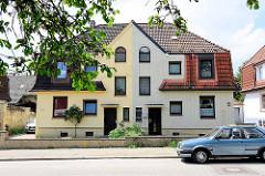 Einstöckiges Doppelhaus mit unterschiedlicher Fassadengestaltung in Hamburg Wilstorf.