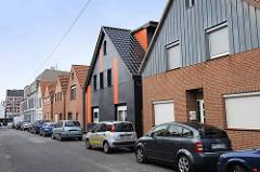Wohnhäuser mit Satteldach gleicher Bauform mit unterschiedlicher Fassadengestaltung in der Surfeldstraße von Bremerhaven.