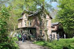 Außenansicht der unter Denkmalschutz stehenden  Villa Mutzenbecher, blühender Rhododendron vor der Holzveranda.