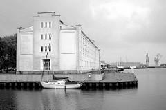 Historische Gewerbearchitektur / Industriearchitektur am Handelshafen von Bremerhafen - davor hat ein kleines Segelschiff festgemacht.