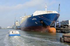 Frachtschiffe liegen am Kai vom Kaiserhafen 1 in Bremerhaven, ein Fahrgastschiff der Hafenrundfahrt passiert den großen Frachter.