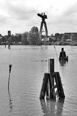 Blick auf die Geeste in Bremerhaven, Holzdalben - Pricken / Fahrwasserkennzeichnung mit Zweigbüscheln zeigen das Fahrwasser an.