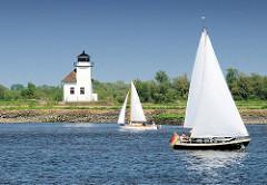 Segelboote mit weissen Segeln auf der Elbe vor dem Leuchtfeuer Julesand.