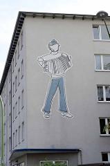 Fassadendekoration an einem Wohnhaus in Bremerhaven - Matrose spielt Akkordeon.