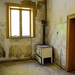 Ehemalige Küche in der Villa Mutzenbecher; ein alter Küchenherd / Holzherd steht an einer gekachelten Wand.