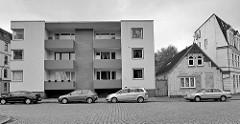 Kubische Architektur Balkons und quadratischen Fenstern - daneben altes Wohnhaus mit Sattedach; Kopfsteinpflaster - Architektur in Bremerhaven / Lehe.