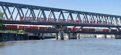 Eisenbahnbrücken am Billehafen / Oberhafenkanal in Hamburg Rothenburgsort; ein Containerzug / Güterzug beladen mit Containern sowie eine S-Bahn überqueren den Kanal.