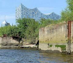Im Krieg zerstörte Kaimauer / Ruine im Reiherstieg in Hamburg Steinwerder - im Hintergrund die Fassade der Elbphilharmonie und die Spitze vom Büroturm HTC.