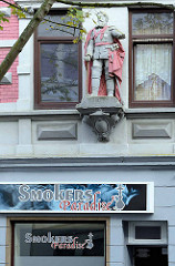 Smokers Paradise - einarmige Kaiserfigur / Offizier mit Orden und Degenals Steinfigur einer Hausfassade in Bremerhaven.