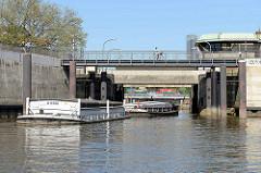 Ein Schleppverband  mit Schuten fährt vom Oberhafenkanal  in die Brandshofer Schleuse ein. Radfahrer auf dem Elberadweg in Hamburg Rothenburgsort.