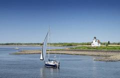 Einfahrt zum Dwarsloch - Haseldorfer Binnenelbe - ein Segelboot unter Segel, blauer Himmel.