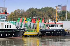 Arbeitsschiffe vom Wasserstraßen- und Schifffahrtsamt Bremerhaven; rote und grüne Fahrwassertonnen am Kai.