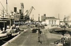 Historische Hafenansicht aus Bremerhaven - ein Passagierschiff liegt am Kai, die Ausleger der Hafenkräne ragen in den Himmel.