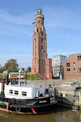 Das Tankmotorschiff Cora liegt in der Schleusenkammer der neuen Schleuse Bremerhaven; im Hintergrund der Leuchtturm / Loschenturm von 1854.