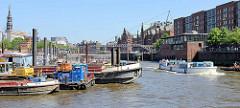 Arbeitsschiffe liegen im Hamburger Binnenhafen,  ein Fahrgastschiff mit Touristen besichtigt  die Speicherstadt - Fußgänger auf der Kehrwiederbrücke.