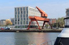 Blick über den neuen Hafen Bremerhaven, ein alter Hafenkran steht als Industriedenkmal am Kai - hinter moderner Architektur eines Wohnhauses.