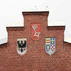 Historisches Gebäude vom Tonnenhof Bremerhaven - Tonnenschuppen mit den Wappen Preußens, Bremens und Oldenburgs.