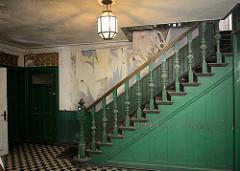 Treppe in der historischen Villa Mutzenbecher, eine alte Lampe beleuchtet den Raum - alter gedrechselter Antrittspfosten und Treppendocken im Stil der Gründerzeit.