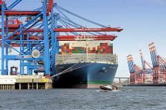 Das Containerschiff MOL TRIUMPH liegt im Hamburger Hafen / Container Terminal Burchardkai; ein Tuckerboot passiert den Bug des Frachters.