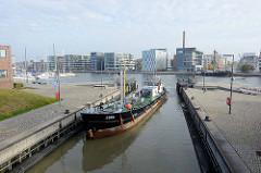 Ein Tankmotorschiff fährt in die Schleuse neuer Hafen ein - im Hintergrund moderne Wohnbebauung am Hafenrand.