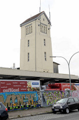 Schlachthofgelände in Lehe / Bremerhaven; Mauer mit Graffiti / Turm mit Spitzdach und Antennen.