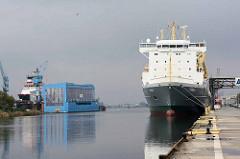 Ein Frachtschiff liegt im Fischereihafen von Bremerhaven; im Hintergrund Werftanlagen.