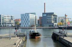 Ein Küsten Frachtschiff / Motorschiff Kümo fährt in die Schleuse neuer Hafen ein.