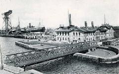 Historische Ansicht von der Drehbrücke am Kaiserhafen in Bremerhaven; ein großer Kran steht auf der Kaianlage.