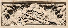 Relief, Sandsteindekor an der Fassade Hamburger Feuerwache Innenstadt; Schlangen symbolisieren das Feuer, in der Mitte Ausstattung eines Feuerwehrmannes.
