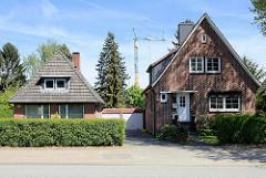 Wohnhäuser / Zielfassade  mit unterschiedlichen Dachformen ( Walmdach +  Satteldach) - miteinander verbundene Garagen.