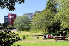 Mittagspause in der Sonne - Grünanlage mit Sitzgelegenheiten in der City Nord.