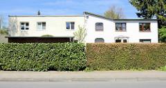 Einstöckige Wohnhäuser mit Flachdach / Schrägdach; unterschiedliche Straßenhecken - Architektur in Hamburg Eidelstedt.
