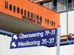 Orangefarbene Fassadengestaltung - Überseering, Hamburg Winterhude - Strassenschilder / Mexikoring.