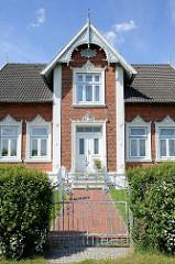 Prächtig restaurierte  Gründerzeitvilla mit Backsteinfassade und farblich abgesetzten Stuckdekor, geschnitzter Ziergiebel aus Holz.