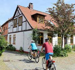 Radtouristen fahren bei ihrer Stadtbesichtigung von Hitzacker über den Kirchplatz der Sankt Johannes Kirche.