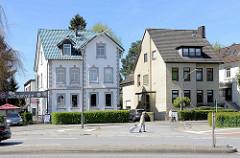 Historische Architektur der Gründerzeit, Wohnhaus mit grünen Dachziegeln, daneben Gebäude mit gelber Ziegelfassade.