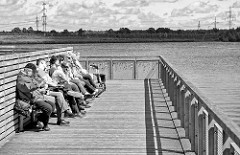 Windgeschützte Uferpromenade - Ruhebänke in der Sonne am See im Norderstedter Stadtpark.