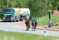 Straßenverkehr am Obergeorgswerder Hauptdeich, ein Tanklastwagen  wartet an der Ampel,  zwei Reiterinnen zu Pferd überqueren die Straße.
