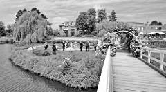 Blick auf die Hochzeitsinsel im See vom Rosarium in Uetersen. Eine Holzbrücke führt über den kleinen See zur Insel.